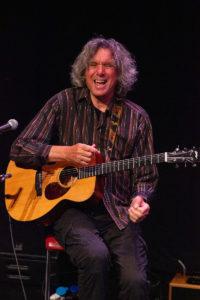John Etheridge smiling and playing guitar