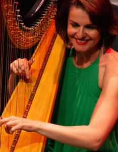 Alina Bzhezhinska playing harp and smiling