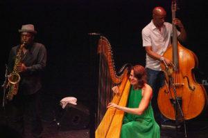 Tony Kofi playing saxophone, Alina Bzhezhinska playing harp, Larry Bartley playing bass on stage at Hull Truck Theatre